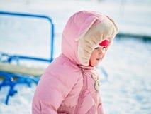 小女孩一岁采取在冬天公园的第一步 免版税图库摄影
