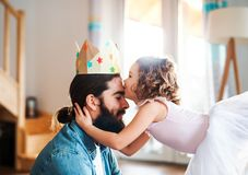 小女孩一张侧视图有在家公主冠和年轻父亲的,使用 库存照片