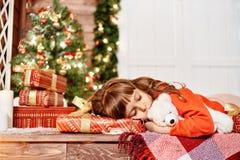 小女孩与在房子门廊的一头玩具熊睡觉在圣诞树 免版税库存图片