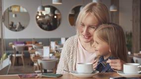 小女孩与她的母亲分享有些秘密 库存照片