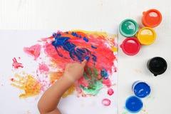 小女孩与油漆刷和五颜六色的油漆儿童发育概念的手绘画 库存照片