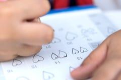 小女孩书面心脏图钉在2月14日华伦泰日期  图库摄影