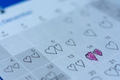 小女孩书面心脏图钉在2月14日华伦泰日期  免版税库存图片