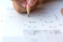 小女孩书面心脏图钉在2月14日华伦泰日期  免版税库存照片