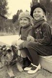 小女孩互相告诉秘密,坐在公共汽车站 免版税库存照片