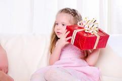 小女孩产生一个节日礼物 图库摄影