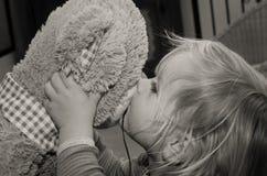 小女孩亲吻熊玩具为再见 免版税图库摄影