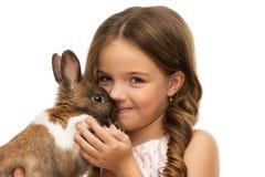 小女孩亲吻的逗人喜爱的棕色兔宝宝 免版税库存照片