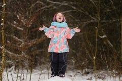 小女孩传染性的雪花在冬天公园 免版税图库摄影