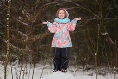 小女孩传染性的雪花在冬天公园 库存照片
