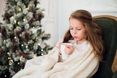 小女孩佩带的睡衣坐在有假日卧具的一条毯子包裹的扶手椅子由圣诞树和壁炉 免版税库存照片