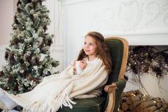 小女孩佩带的睡衣坐在有假日卧具的一条毯子包裹的扶手椅子由圣诞树和壁炉 免版税图库摄影