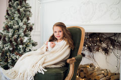 小女孩佩带的睡衣坐在有假日卧具的一条毯子包裹的扶手椅子由圣诞树和壁炉 免版税库存图片