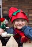 小女孩佩带的矮子帽子和拿着矮子玩具 免版税图库摄影