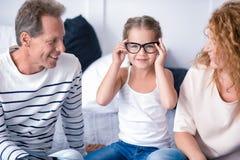 小女孩佩带的玻璃和微笑与她的祖父母 免版税库存照片