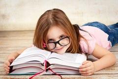 年轻小女孩佩带的玻璃和读书 库存图片