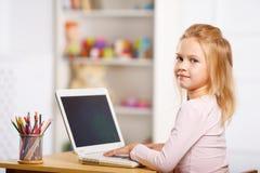 小女孩使用一台膝上型计算机 库存图片