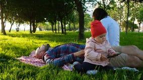 小女孩使用与一个智能手机本质上 年轻家庭在公园休息 免版税库存照片