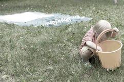 小女孩使用与一个空的桶 免版税图库摄影