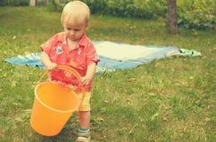 小女孩使用与一个空的桶 免版税库存图片
