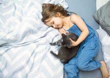 小女孩使用与她的在床上的猫 免版税库存照片