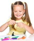 小女孩使用与彩色塑泥 库存照片