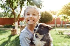 小女孩使用与狗 一条狗作为对孩子的一件礼物 儿童在自然的` s微笑 免版税图库摄影