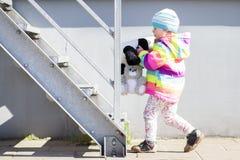 小女孩使用与长毛绒玩具在明亮的晴朗的下午的金属楼梯附近 库存图片