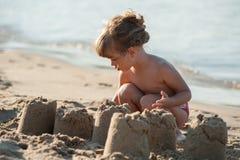 小女孩修造沙子城堡 免版税库存图片