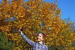 小女孩做在公园秋天季节的selfie 免版税库存图片