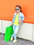 小女孩儿童佩带太阳镜和牛仔裤衣裳有购物袋的 免版税图库摄影