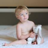 小女孩充当与玩具熊的床 免版税库存照片