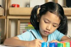 小女孩写着与非常集中的一本书 免版税库存图片