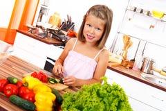 小女孩剪切蔬菜 免版税库存图片