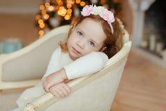 小女孩卷曲婴孩坐在椅子和哀伤在圣诞节 免版税库存照片