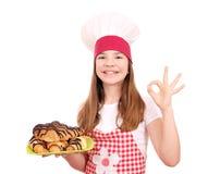 小女孩厨师和新月形面包用巧克力在板材 免版税库存照片