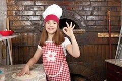 小女孩厨师在比萨店 免版税库存图片