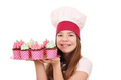 小女孩厨师用在板材的松饼点心 免版税库存图片