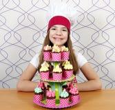 小女孩厨师用在桌上的甜松饼 库存图片
