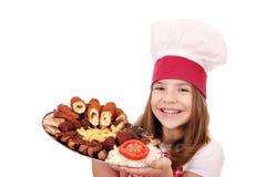 小女孩厨师用混杂的烤肉 免版税库存图片