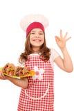小女孩厨师用炸玉米饼和好手签字 免版税库存图片