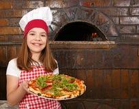 小女孩厨师用薄饼在比萨店 库存图片