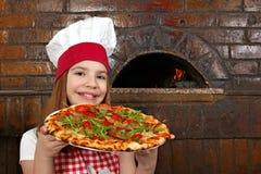 小女孩厨师用薄饼在比萨店 免版税图库摄影
