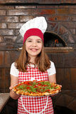 小女孩厨师用薄饼在比萨店 免版税库存照片