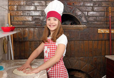小女孩厨师真正的薄饼在比萨店 库存图片