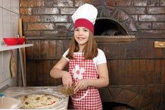 小女孩厨师真正的薄饼在比萨店 免版税库存图片