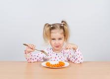 小女孩吃与叉子的红萝卜 免版税库存照片