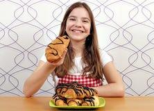 小女孩吃新月形面包用巧克力 免版税库存图片