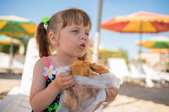小女孩吃果仁蜜酥饼,肮脏的面孔 库存照片