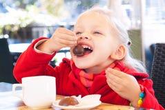小女孩吃甜点并且喝在咖啡馆的茶 免版税库存图片